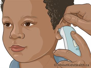 Boy having his temperature taken by ear with one hand holding the ear up  and the